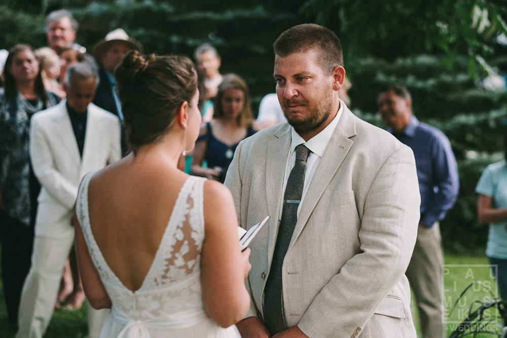 groom cries while listening to wows during wedding ceremony in rural Wisconsin outside of Madison