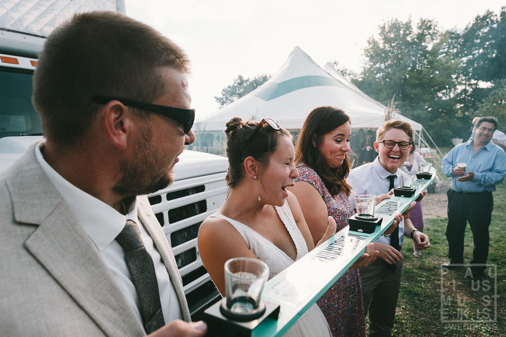guests are doing ski shots at the outdoor reception in rural DIY family farm wedding Wisconsin