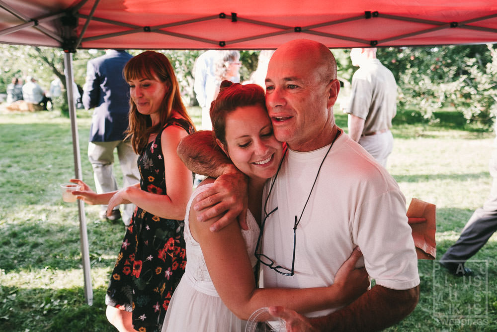 guests are hugging at the outdoor wedding reception in rural Wisconsin outside of Madison