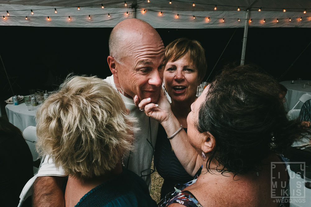 wedding guests are hugging on the dance floor at the wedding reception in rural Wisconsin