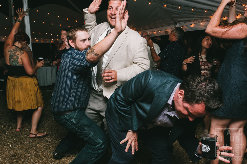 group of groom's friends is performing a dance at the wedding reception in rural Wisconsin