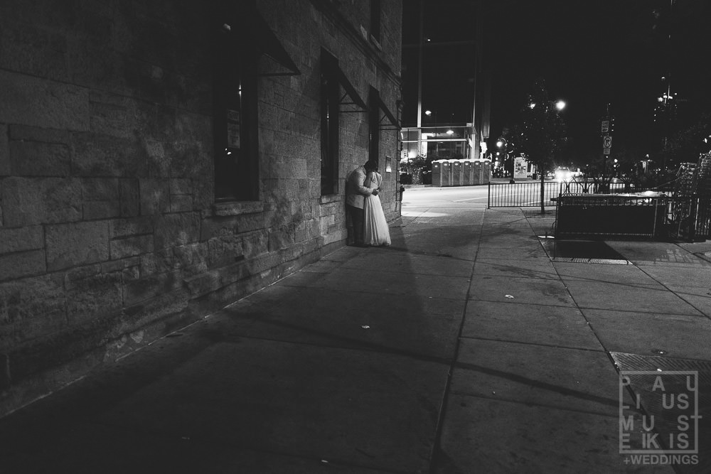 bride and groom are making out in the dark alley on their way to the hotel
