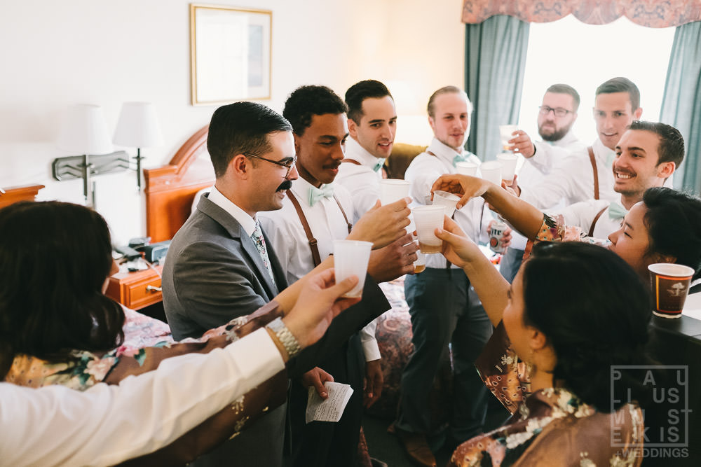 groomsmen taking whiskey shots in hotel room before leaving for the ceremony