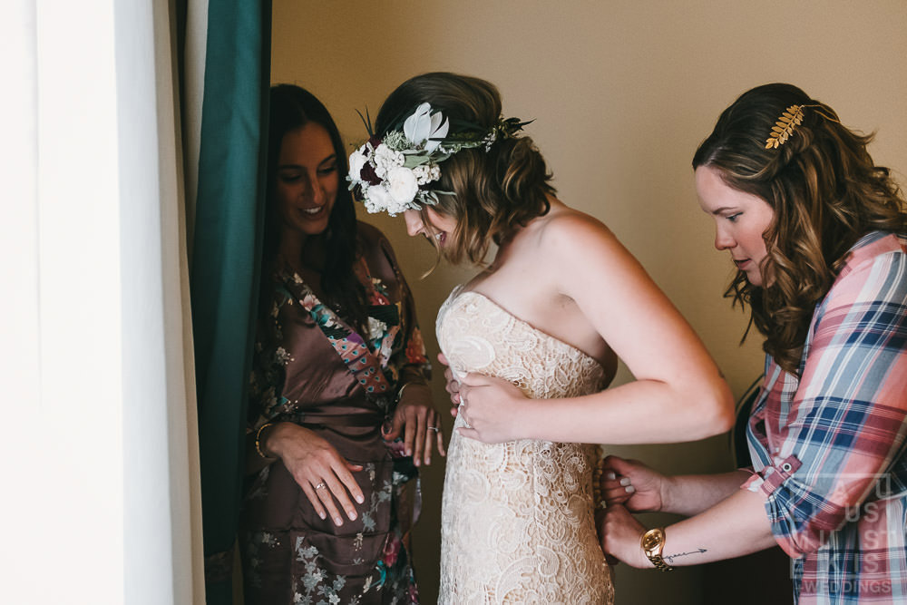 bridesmaids are helping the bride to put the wedding dress on