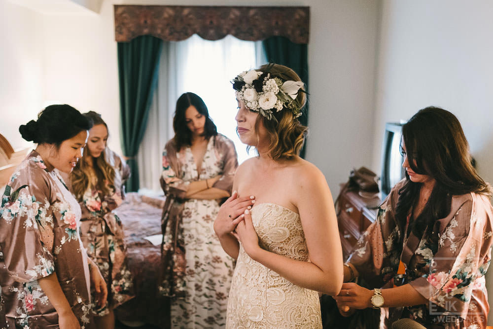 bride is tearing up surrounded by her bridesmaid s in a hotel room