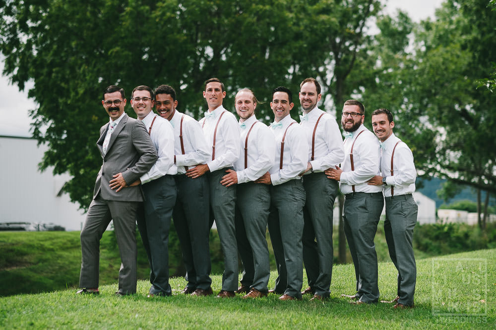 groom and groomsmen doing silly posing in front of the hotel
