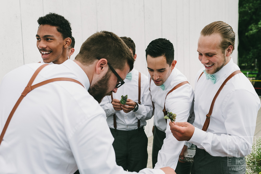 groomsmen getting their boutonnieres pinned in