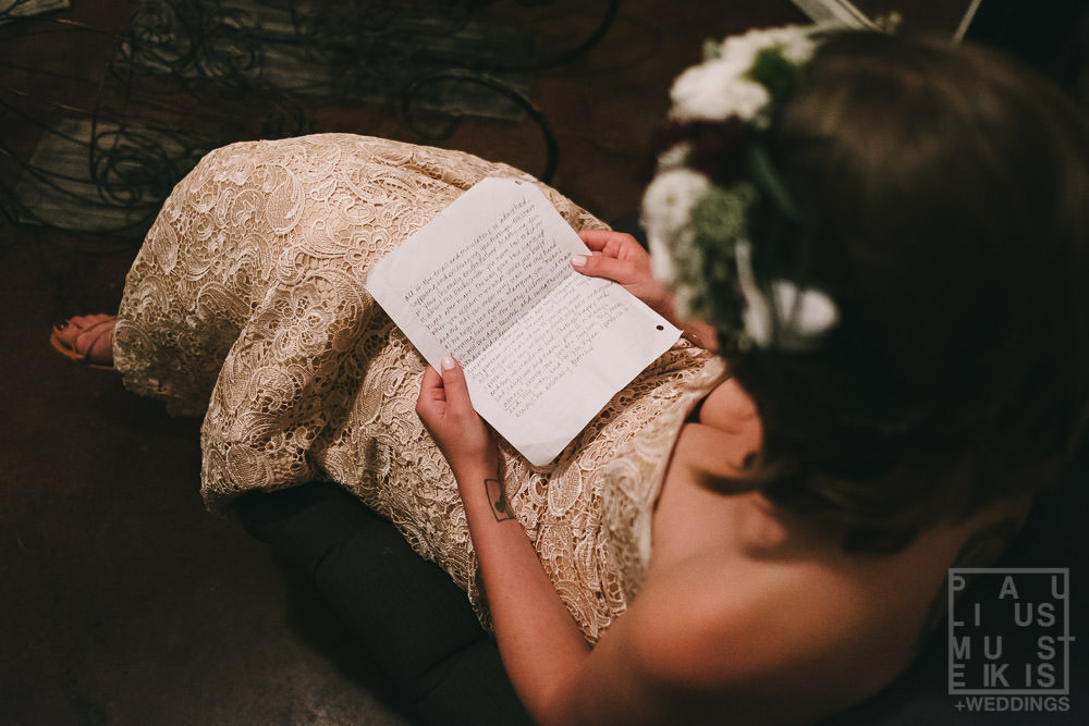 bride is reading her wows in solitude in small room at the Gatherings on the Ridge barn before the wedding ceremony begins