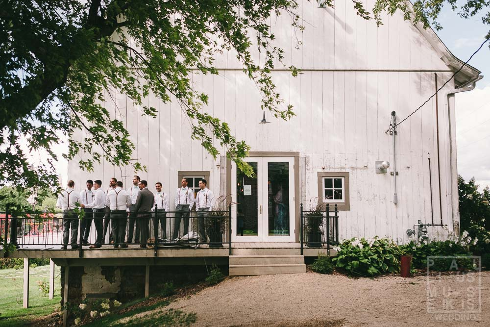 Groom and groomsmen are waiting in barn balcony for the wedding ceremony to begin