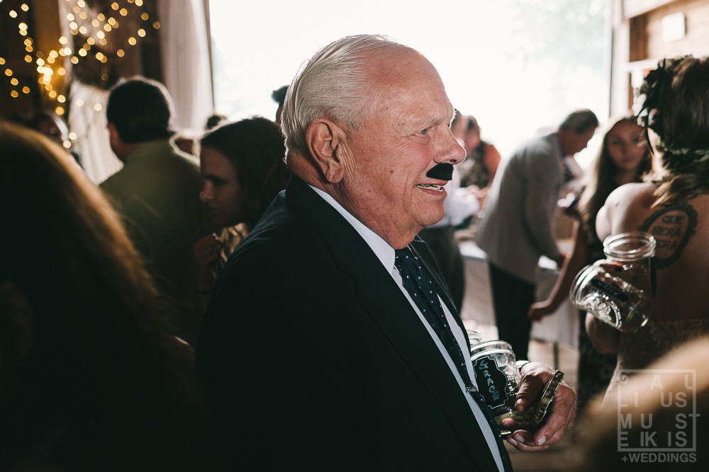 grooms grandfather is impersonating the groom by wearing black fake mustache