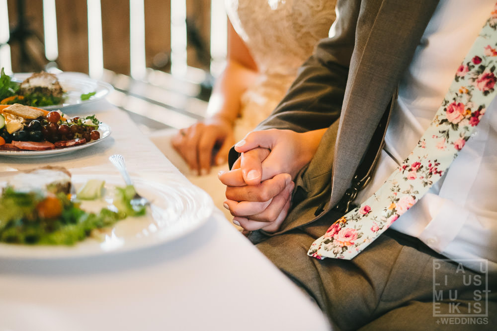 bride and grooms hands together during wedding dinner reception and speeches