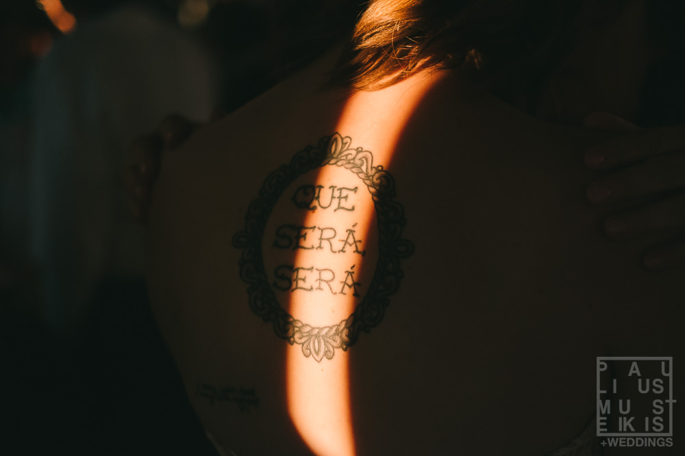 "bride's tattoo that says ""que cera cera"" being lit by sunset light at the Gatherings on the Ridge"