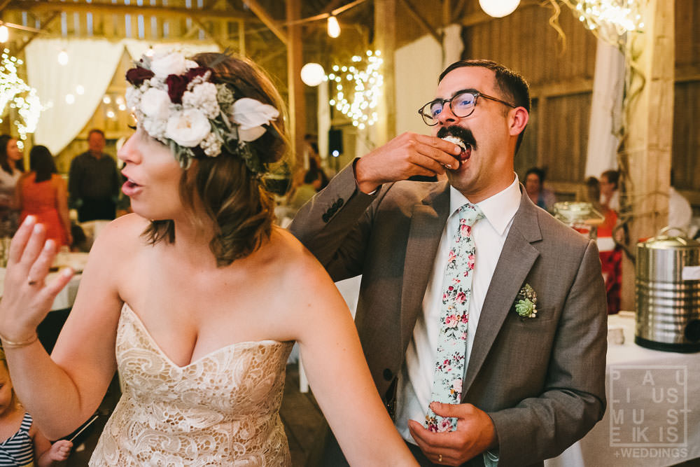 groom making funny face while eating wedding cake