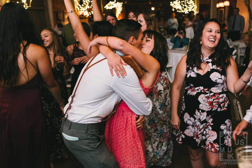 wedding guests are kissing on the dance floor during the reception at the Gatherings on the Ridge barn