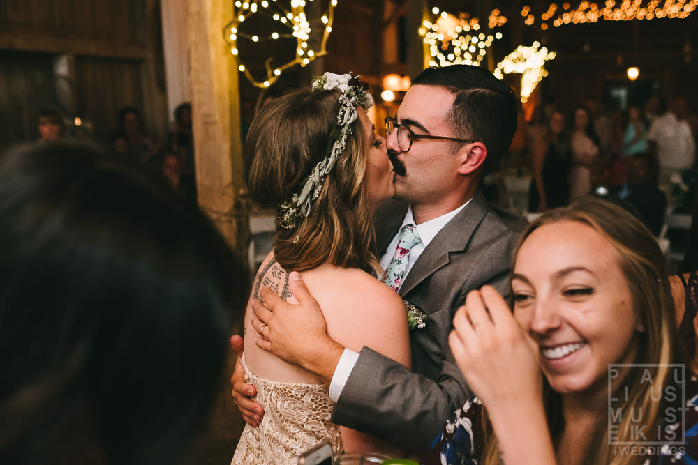 bride and groom are kissing on the dance floor surrounded by dancing wedding guests