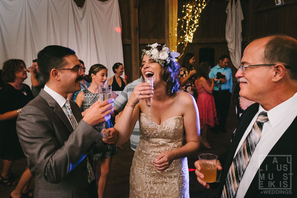 bride and groom are drinking champagne on the dance floor and laughing hard