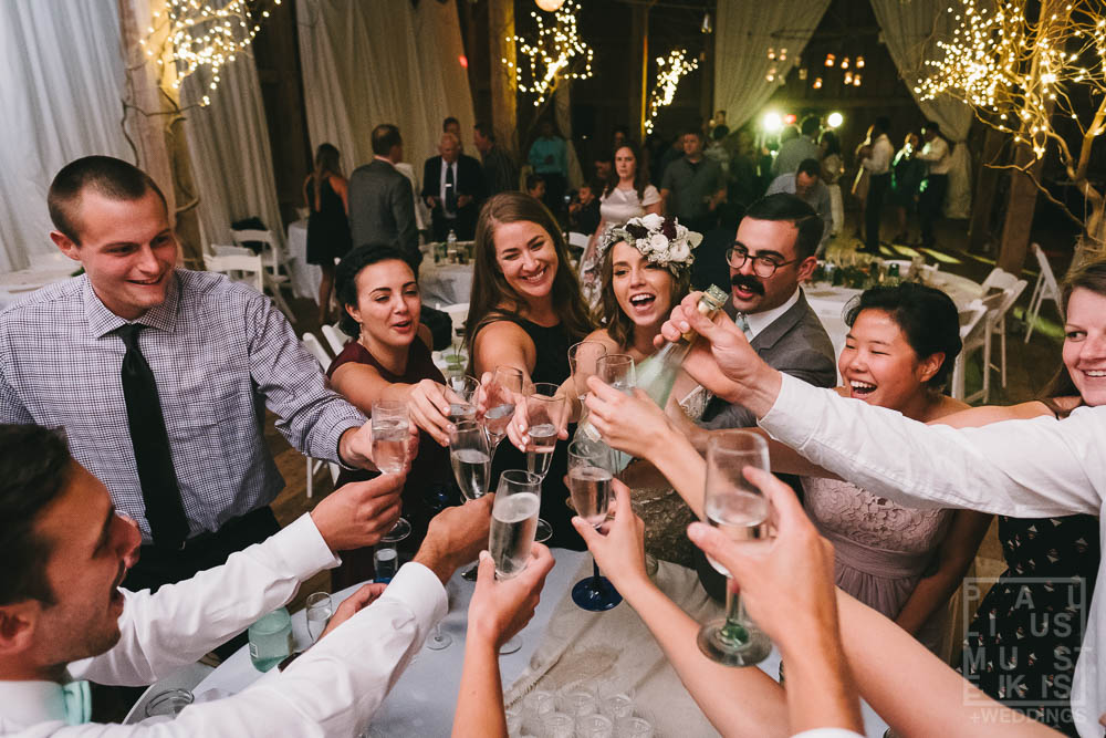 bunch of wedding guests are raising champagne glasses for a toast