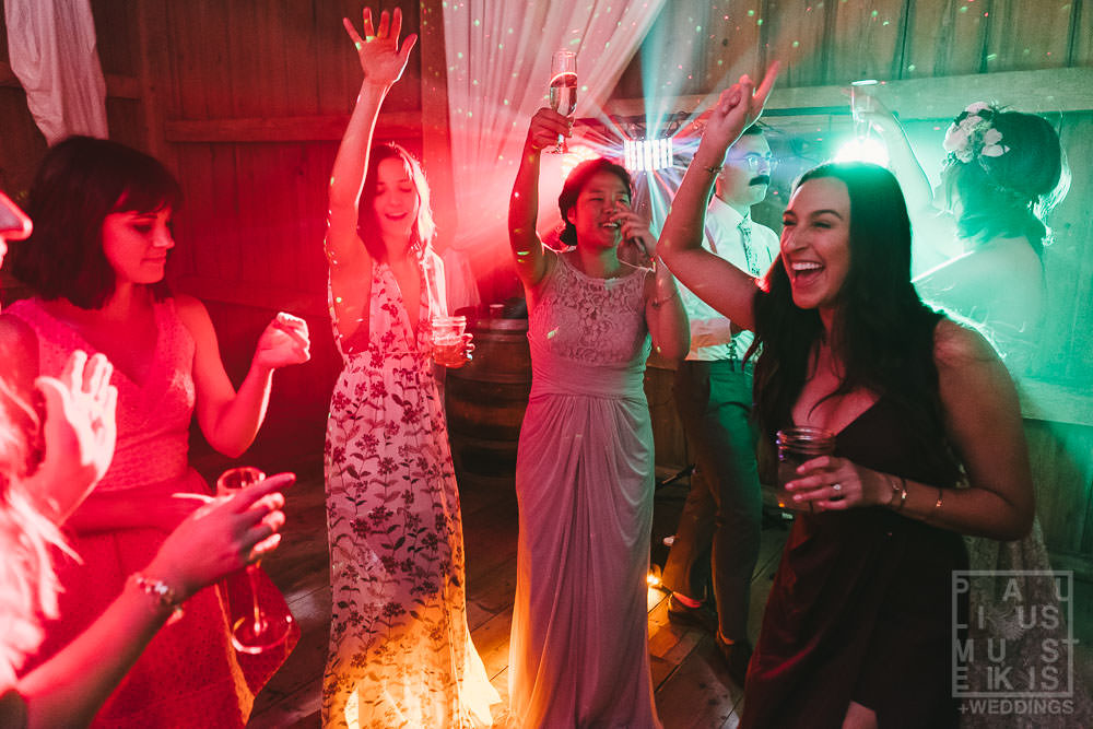 bridesmaids are waving and dancing surrounded by fog and lasers