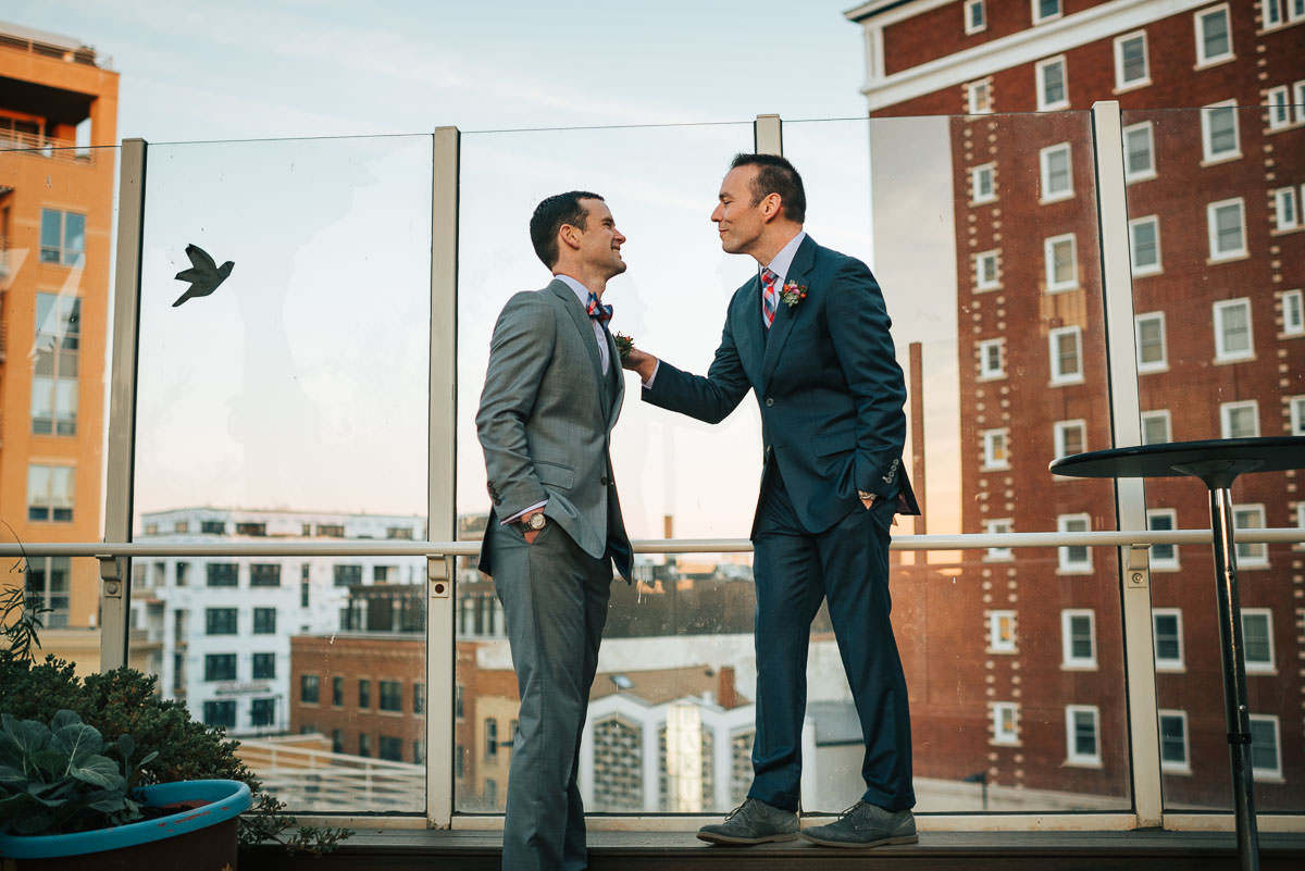 an example of wedding photography style: photojournalism. groom and groom having a private moment