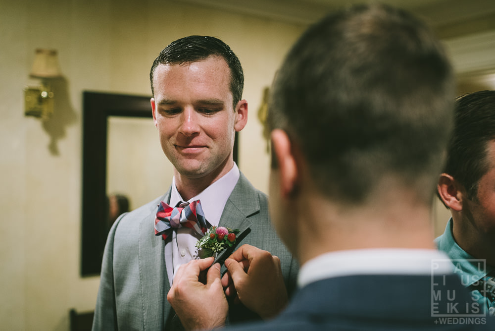groom is getting his flower boutonniere pined in