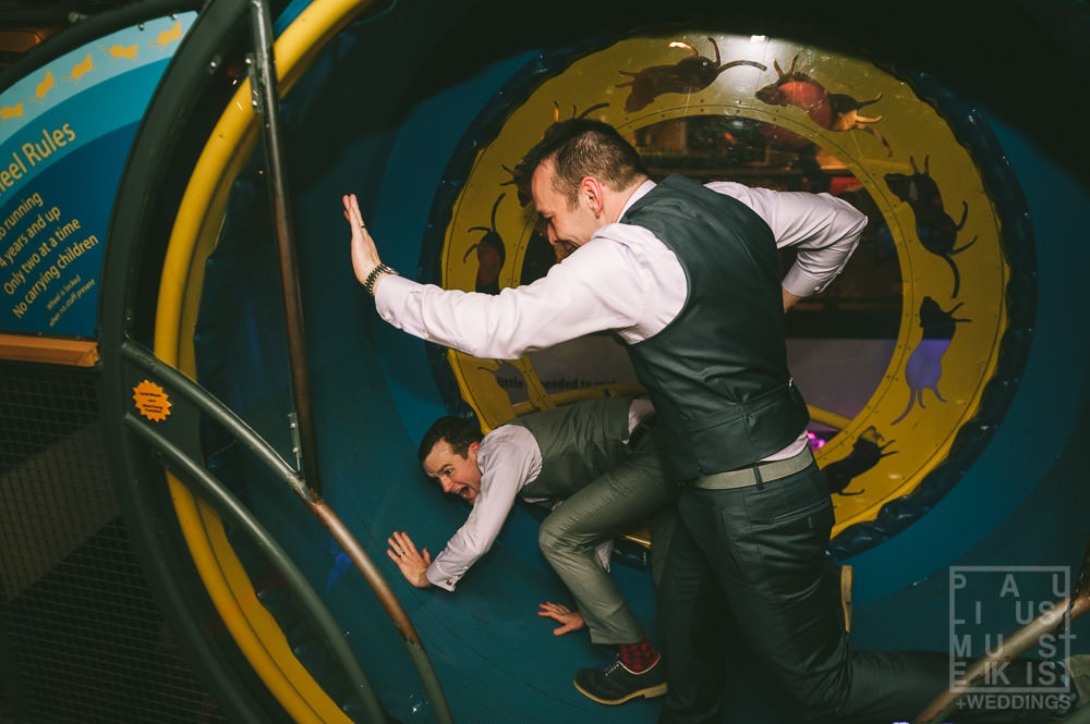 groom and groom are running inside giant hamster wheel during their LGBTQ wedding at the Madison Children's museum in Wisconsin