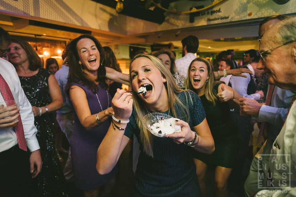 young woman is eating the cake while dancing on the dance floor