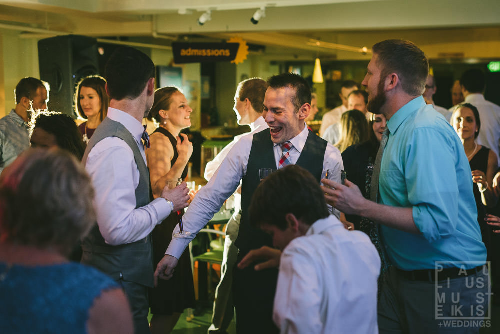 groom is dancing with wedding guests at the Madison Children's museum