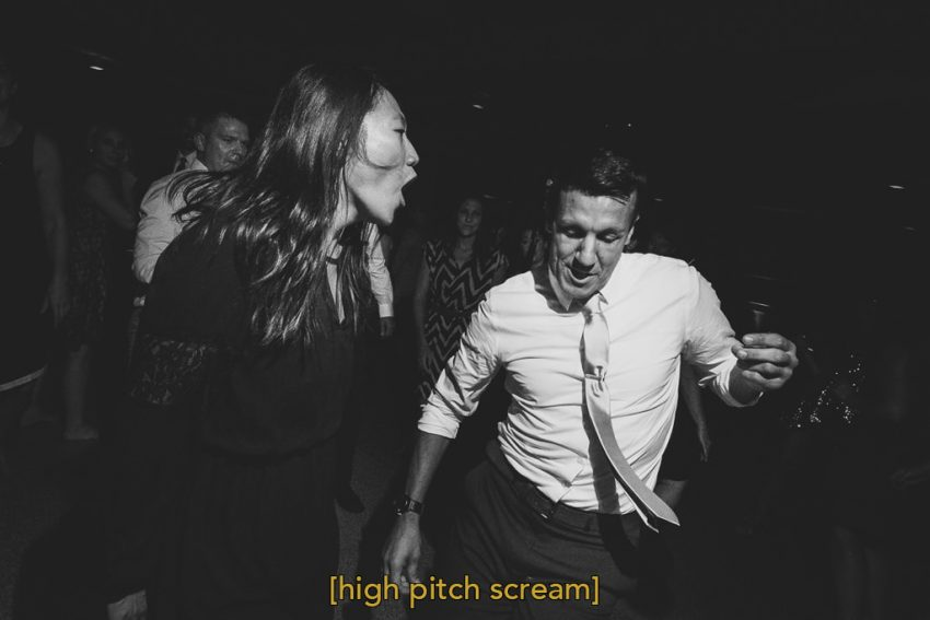 woman is screaming and singing while dancing on the dance floor with the groom at the Milwaukee New Years Eve wedding