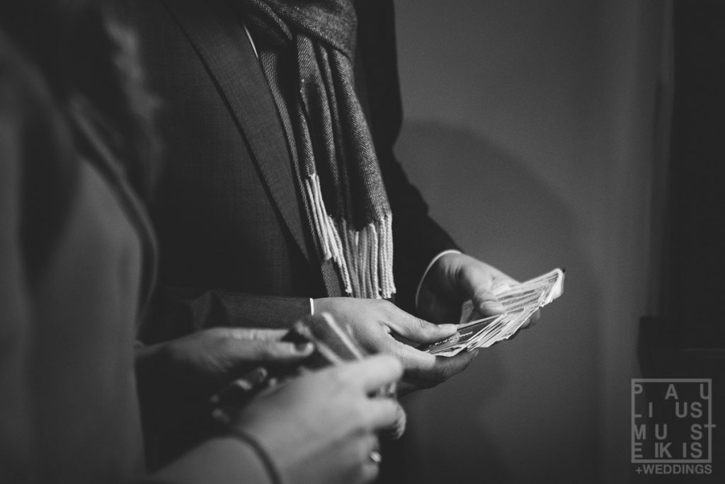 bride's and groom's hands holding cash exemplifies one of more important wedding planning tips- don't go into debt