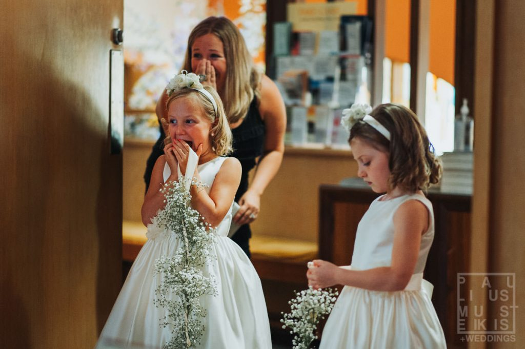 an example of wedding photojournalism: flower girls are very excited about bride and groom