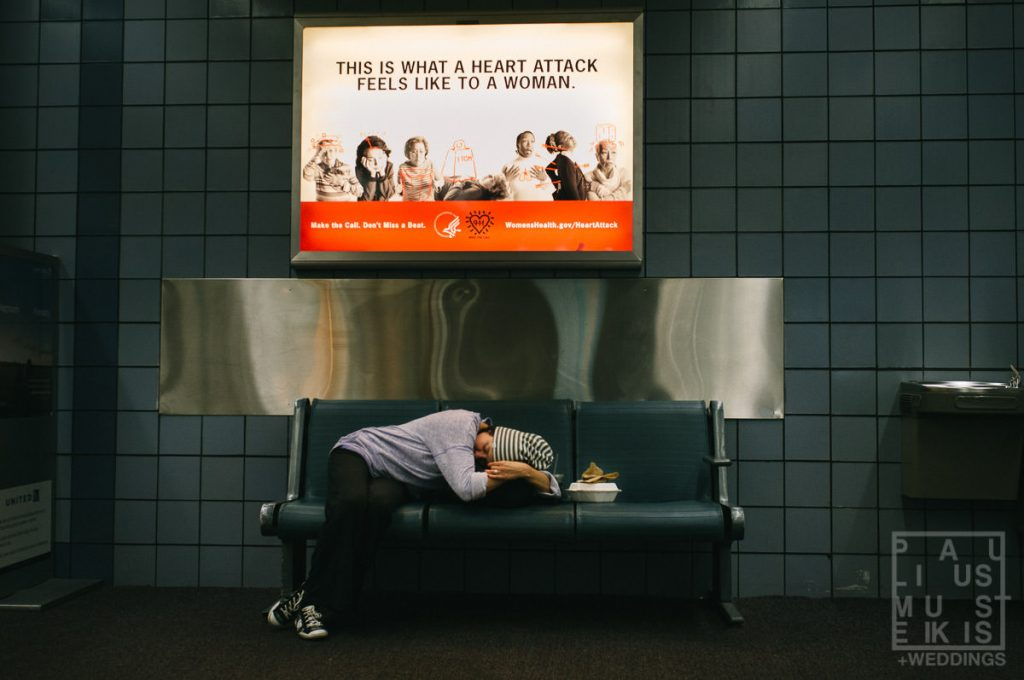 woman sleeping on chairs in airport with funny sign above her