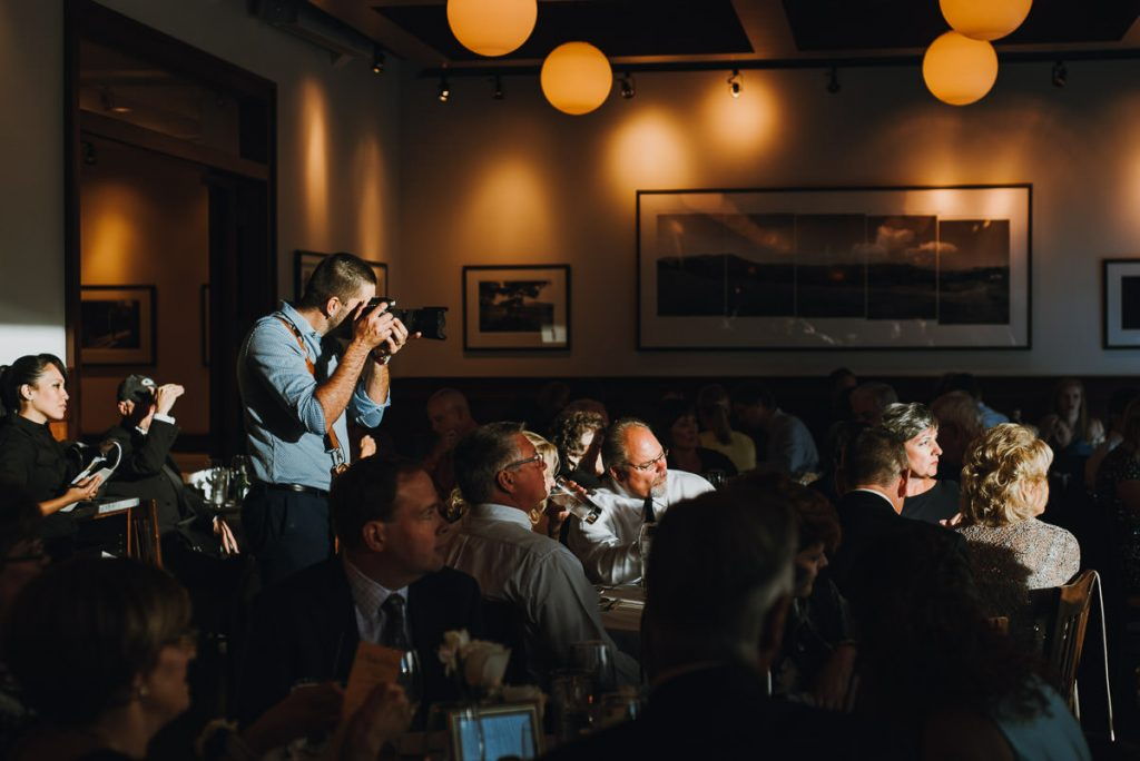 candid portrait of wedding photographer with camera at wedding reception in Madison, WI