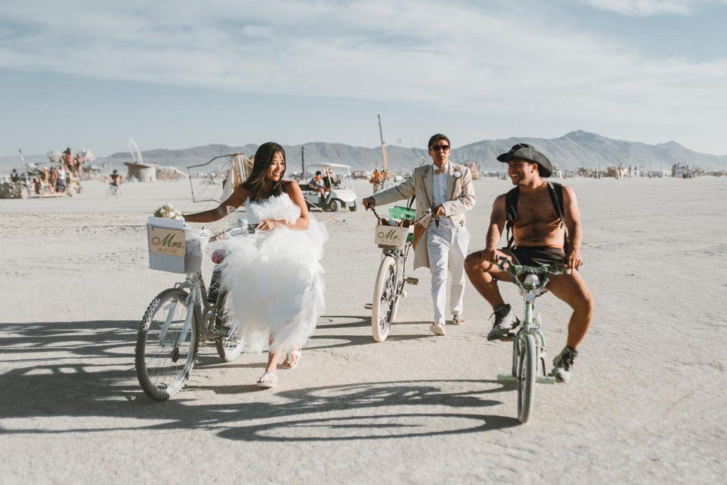 bride and groom biking to their wedding ceremony during Burning Man festival in Black Rock desert, Nevada