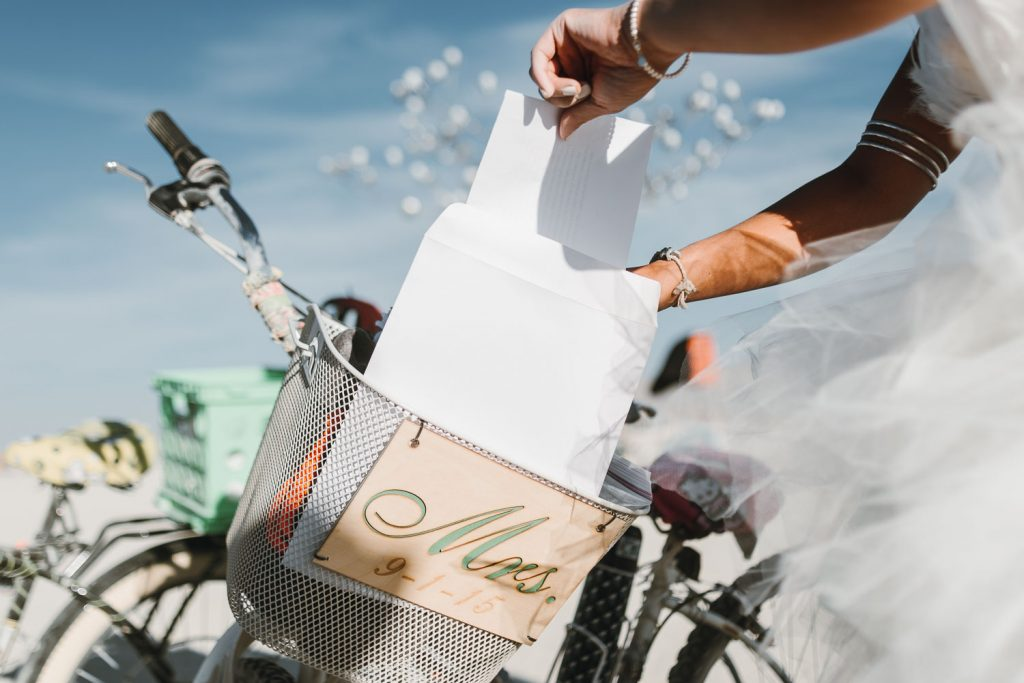 candid image of bride Sandi getting wedding paperwork out of the bike basket for her Burning Man wedding photography in Black Rock desert, Nevada