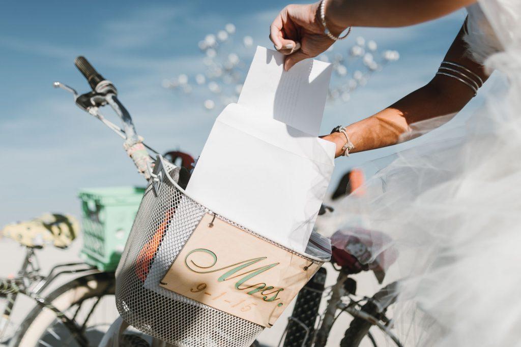candid image of bride Sandi getting wedding paperwork out of the bike basket for her Burning Man wedding photography in Black Rock desert, Nevada