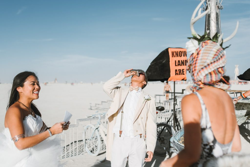 groom taking a sip of bourbon from the flash before his wedding ceremony at the Burning Man festival in Black Rock desert, Nevada