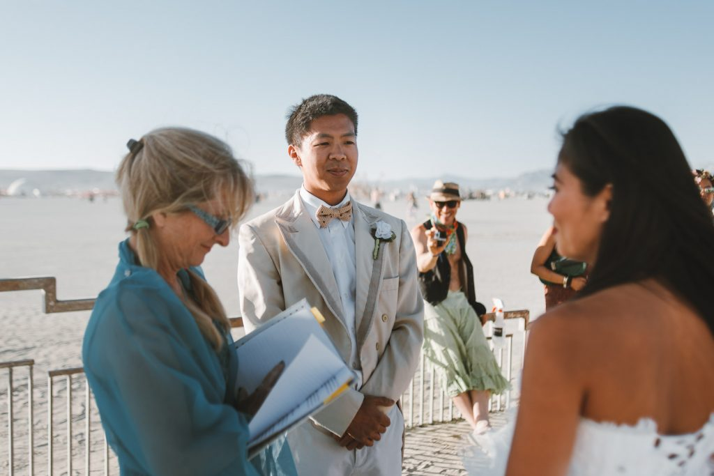 smiling groom looking at the bride during Burning Man wedding ceremony in Black Rock desert, Nevada