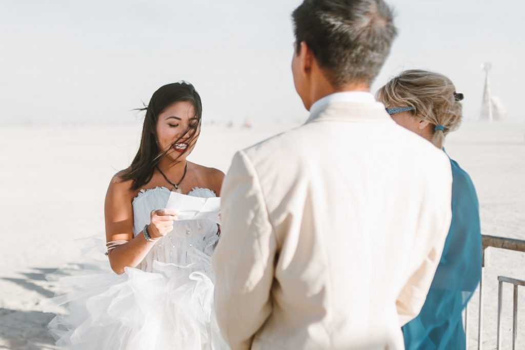 bride reading her wedding vows to the groom during Burning Man wedding ceremony in Black Rock desert, Nevada