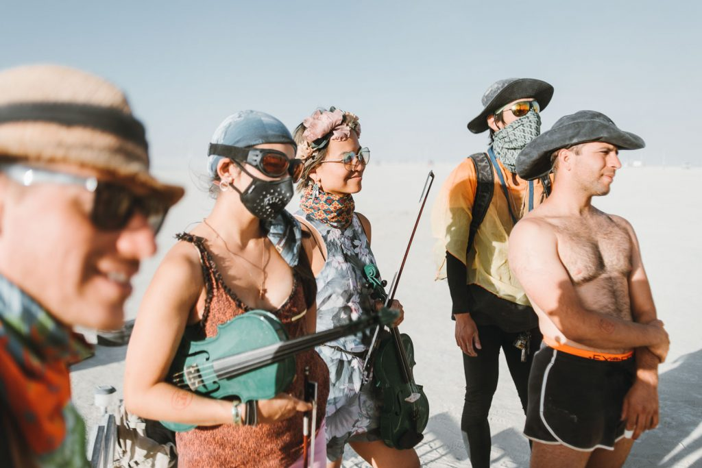 smiling ceremony attendees during Burning Man wedding ceremony in Black Rock desert, Nevada