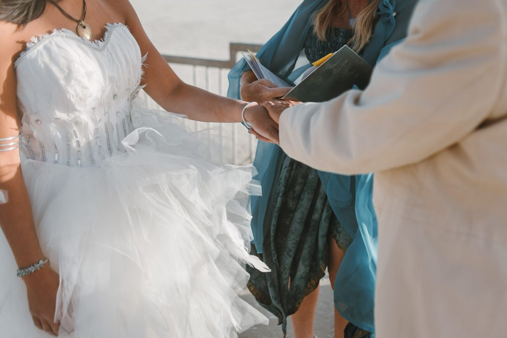 groom is putting a ring on bride's finger during Burning Man wedding ceremony in Black Rock City