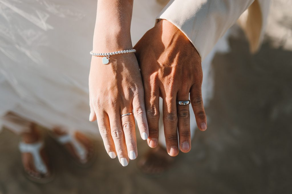 bride's and groom's dusty hands with wedding rings on them after the Burning Man wedding ceremony