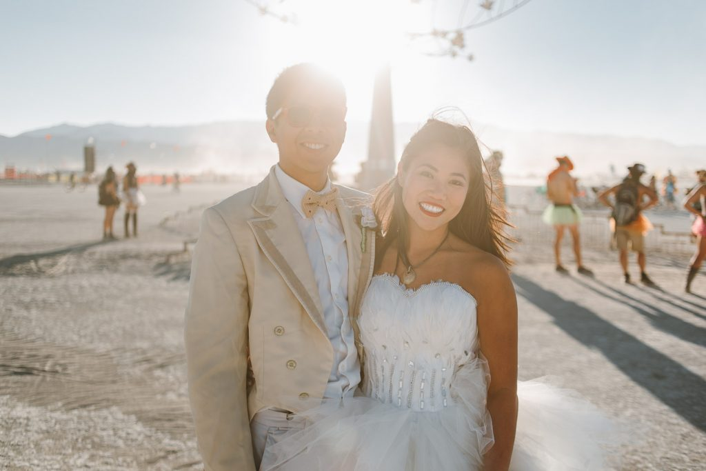 bride and groom portrait while posing in front of Infinity Tree art piece during Burning Man festival in Black Rock desert, Nevada