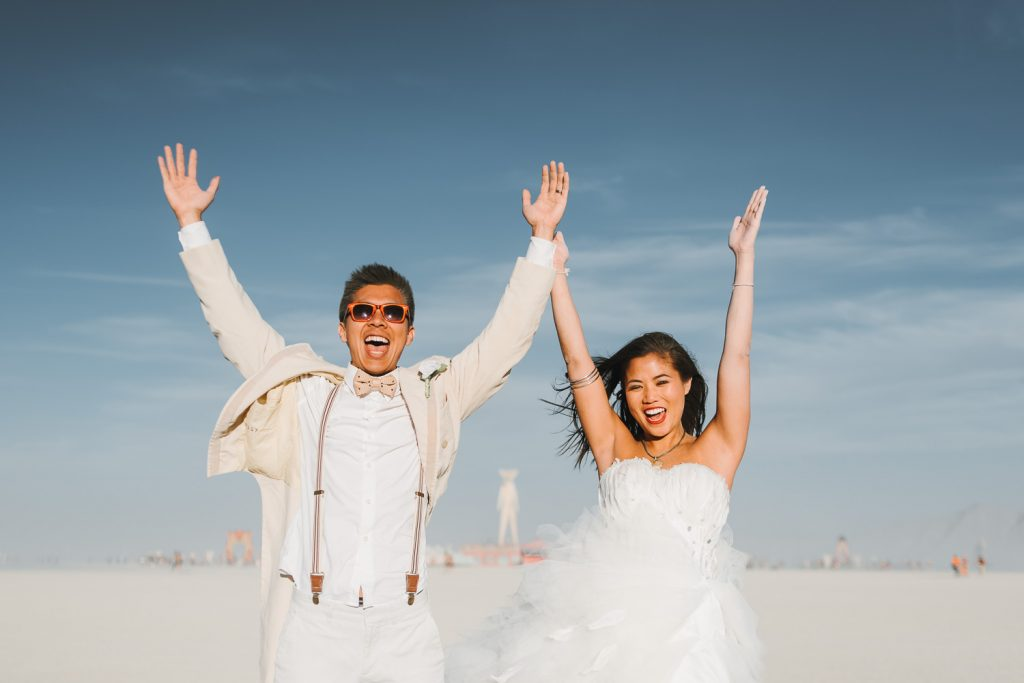 bride Sandi and groom Andy are happy screaming out loud with the Burning Man statue in the background at the Black Rock desert, Nevada