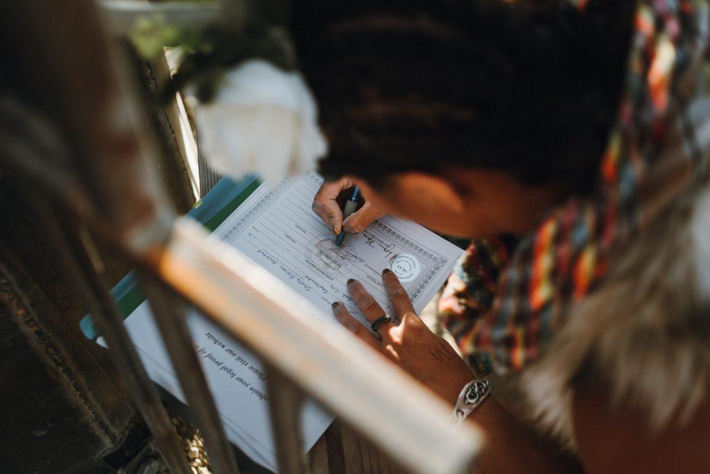 wedding witness is signing wedding documents after the Burning Man wedding ceremony in Black Rock desert, Nevada