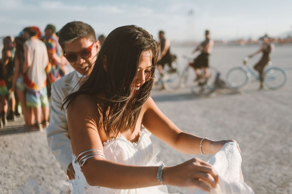 candid picture of bride and groom after their wedding ceremony during Burning Man festival in Black Rock desert, Nevada