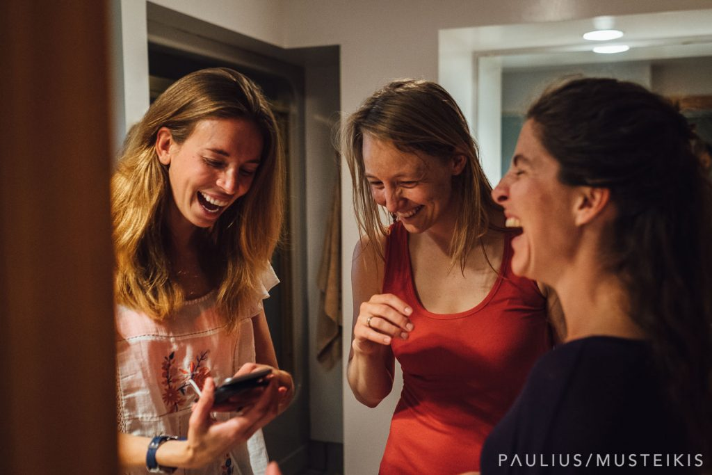 bride is laughing with her bridesmaids while getting ready for the wedding ceremony