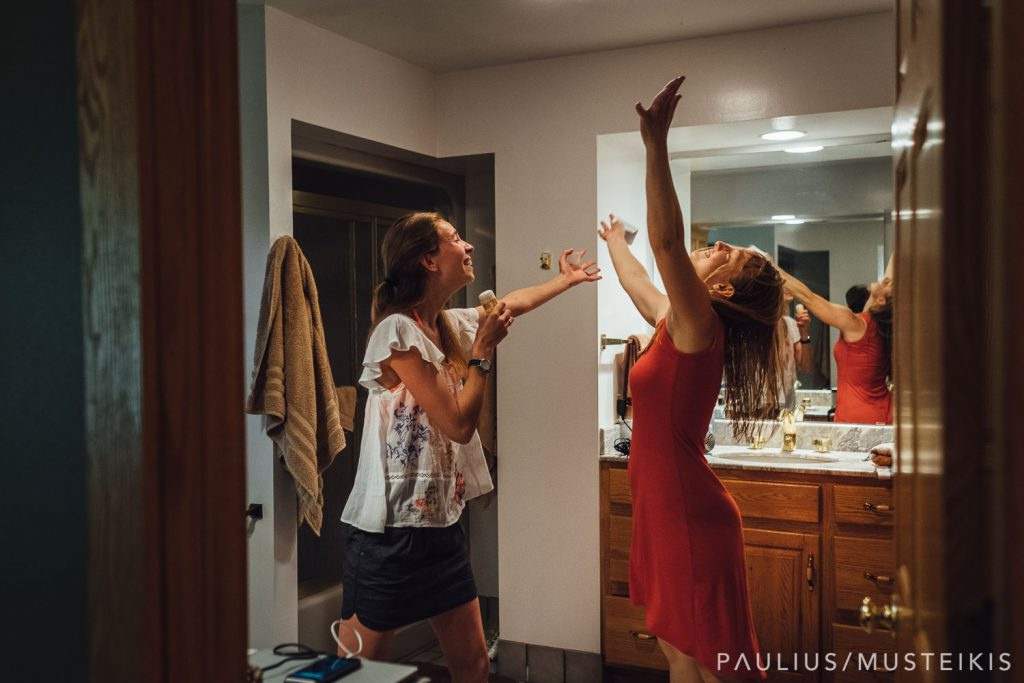 bride and her bridesmaid are dancing and singing into deodorant stick while getting ready for Wisconsin river wedding ceremony