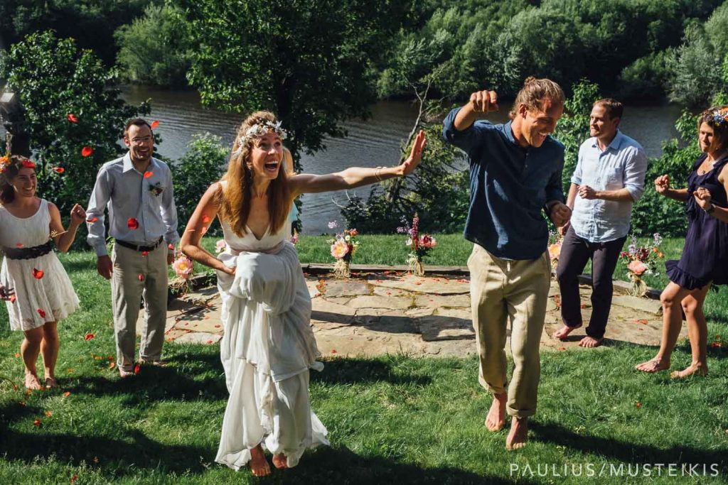 bride and groom are making funny faces while walking away after the Wisconsin river wedding ceremony