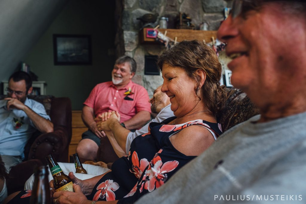 mother of the groom laughing during the gathering in living room area