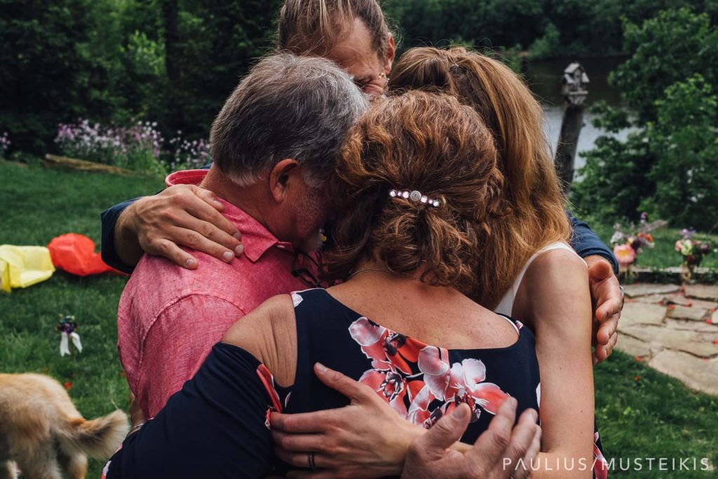 bride, groom and groom's parents are doing a group hug after the wedding ceremony